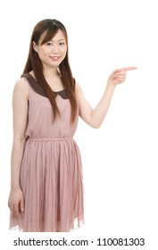 Smiling young asian businesswoman pointing