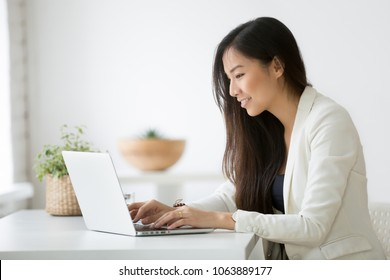 Smiling young asian businesswoman using computer at home office workplace, happy korean employee working on laptop, attractive japanese or chinese woman student studying communicating online with pc