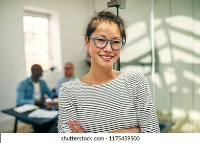 Smiling young Asian businesswoman wearing glasses standing in an office with her arms crossed with colleagues working in the background