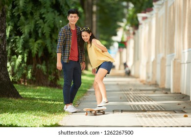 Smiling young Asian couple spending Sunday in summer park