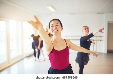 Smiling young Asian dance teacher leading a group of senior women during a ballet class in a dance studio