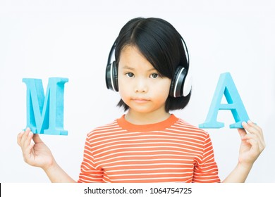 smiling young asian female kid using headphone wireless for listen online e-learning phonics english sound to studying english in classroom.