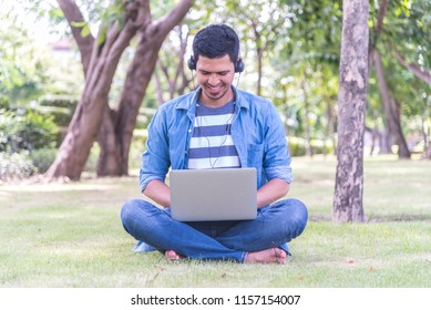 Smiling young Asian man in headphones sitting in the park and looking at laptop screen watching webinar - Education self learning concept