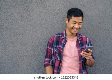 Smiling young Asian man leaning against a gray wall outside reading a text message on his cellphone