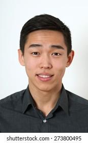 Smiling young Asian man looking at camera.