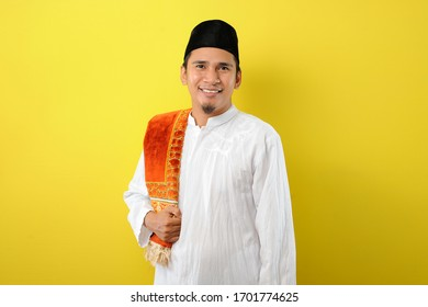 Smiling Young Asian Muslim man standing over yellow background
