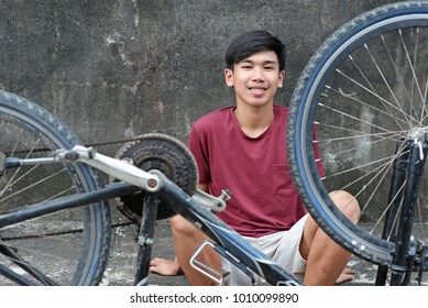Smiling young asian teenager sitting at the roadside with an old bicycle.