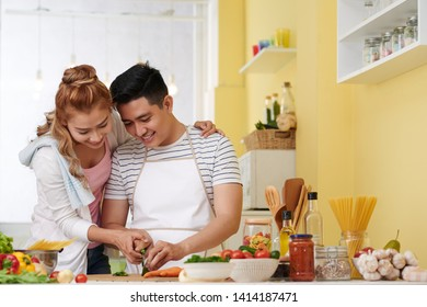 Smiling young Asian woman helping husban with cutting vegetable for salad or soup