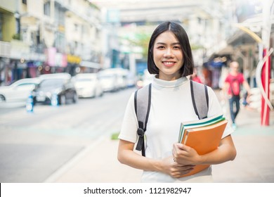 Smiling young asian woman with her book backpack in the city. Portrait of beautiful asian girl walking to school. Education tutor authentic lifestyle people back to school concept