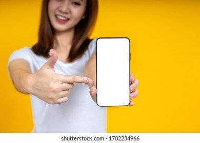 Smiling young Asian woman is pointing on smartphone standing on yellow background.