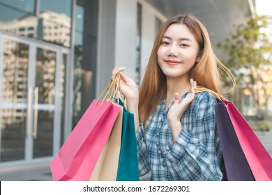 Smiling young Asian woman with shopping colour bags over mall background. using a smart phone shopping online  and smiling while standing mall building. lifestyle concept