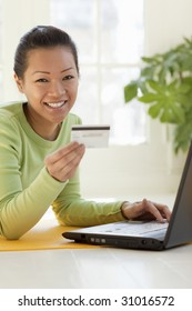 Smiling young Asian woman shopping on-line with credit card and laptop computer