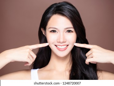 smiling young asian woman showing her teeth