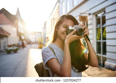 Smiling young Asian woman taking photographs with a vintage slr camera while walking around the city in the afternoon