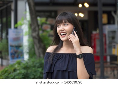 smiling young asian woman talking on smart phone in the city