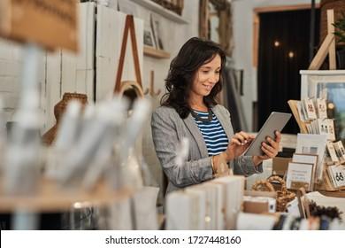 Junge Asiatinnen lächeln mit einem digitalen Tablett, während sie hinter einer Theke in ihrer stilvollen Boutique stehen