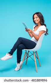 Smiling young asian woman using tablet pc computer while sitting on the chair isolated on the blue background