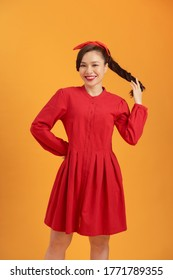 Smiling young Asian woman wearing red dress isolated over orange background.