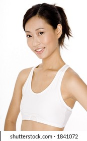 A smiling young asian woman in white sports bra on white background