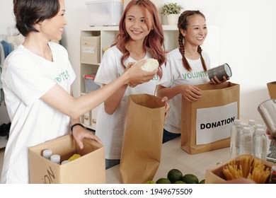Smiling young Asian women packing canned food, fruits, vegetables and waterr in paper packages to donate in charitable center
