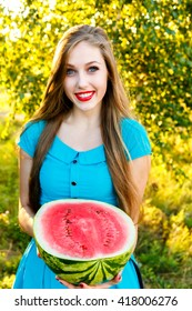 Smiling young attractive blonde girl holding half of ripe watermelon outdoors