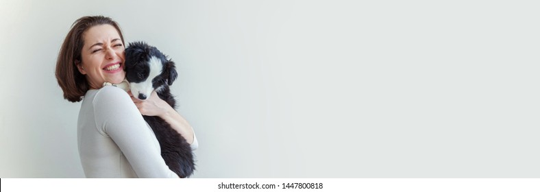 Smiling young attractive woman embracing cute puppy dog border collie isolated on white background. Girl huging new lovely member of family. Pet care and animals concept. Banner