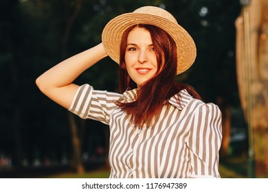 smiling young attractive woman wearing striped dress and straw hat