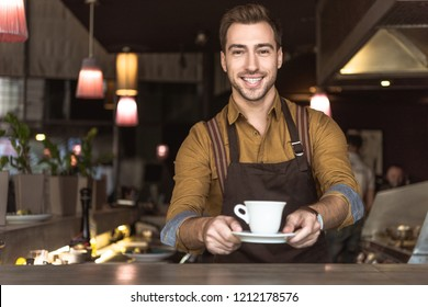 smiling young barista holding cup of coffee and looking at camera