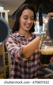 Smiling young barmaid pouring drink from tap in glass at restaurant