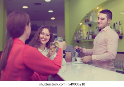 Smiling young bartender and two women with wine at bar. Focus on girl