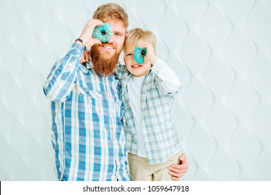 Smiling young bearded hipster man with his cute son having fun while holding donuts on their eyes over white background.