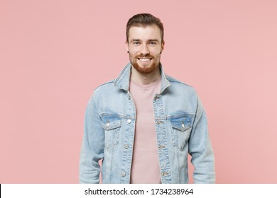 Smiling young bearded man guy in denim casual jacket posing isolated on pastel pink wall background studio portrait. People sincere emotions lifestyle concept. Mock up copy space. Looking camera