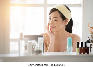 Smiling young beautiful asian woman fresh healthy skin looking on mirror with serum and lotion set at home.facial beauty and cosmetic concept