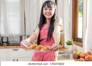 Smiling young beautiful Asian woman girl with apron holding a tray of fresh tasty croissant in homey kitchen. Attractive teenage girl enjoying and having fun learning baking and cooking class at home.