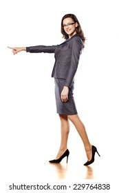 smiling young beautiful business woman pointing at blank