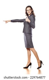 smiling young beautiful business woman pointing at blank and showing thumb up