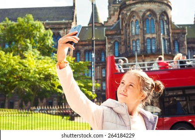 Smiling young beautiful girl taking self portrait in Glasgow historical place. Traveling. Summertime outdoors.