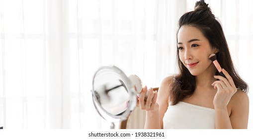 Smiling of young beautiful pretty asian woman clean fresh healthy white skin looking at camara.asian girl holding make-up brushes and make up on face with cosmetics set at home.facial beauty