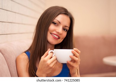 Smiling young beautiful woman with coffee Cup sitting in cafe.