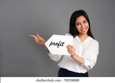 Smiling young beautiful woman in a white shirt holding a white pointer with inscription profit on a gray background