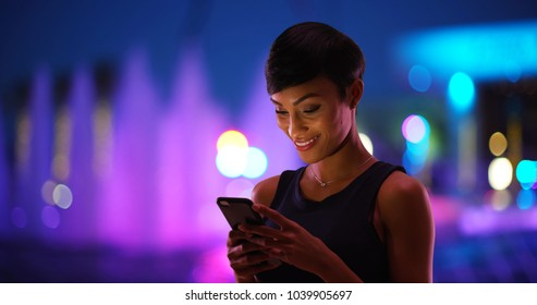 Smiling young black woman texting on cell phone colorful fountain in background