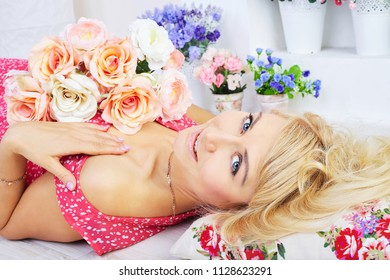 Smiling young blond model posing among flowers