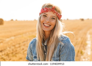 Smiling young blonde girl in headband at the wheat field