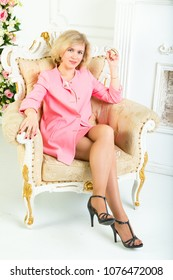 smiling young blonde lass wearing pink skirt suit sitts in a comfortable armchair