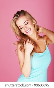 Smiling young blonde woman in blue against a pink background