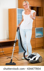 Smiling young blonde woman in jeans vacuuming floor at home