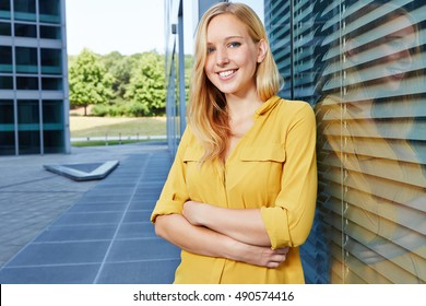 Smiling young blonde woman leaning with her arms crossed in a city
