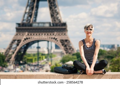 Smiling young blonde woman portrait in front of the Eiffel Tower in Paris, France. Filtered image.