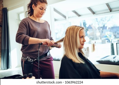 Smiling young blonde woman sitting in a chair in a salon having her hair straightened by her hairstylist