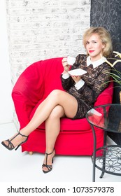 Smiling young blonde woman sitting in a comfortable armchair and drink coffee
